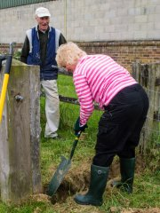 Barbara shows Len how to dig holes.